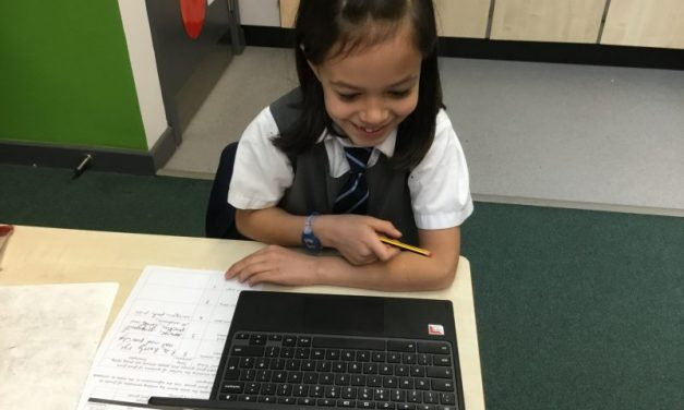 A Year 3 pupil is so happy using the chrome-books to research different food types in science.